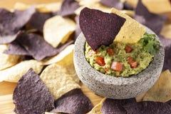 O granito Mulcajete encheu-se com o guacamole fresco cercado por microplaquetas de tortilha azuis e amarelas foto de stock