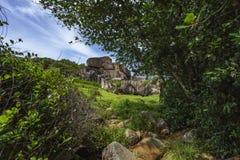 O granito vermelho poderoso balança na grama verde luxúria no songe do anse, la d Foto de Stock Royalty Free