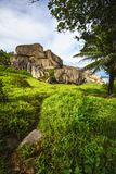 O granito vermelho poderoso balança na grama verde luxúria no songe do anse, la d Imagens de Stock