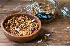 O granola do coco na bacia de madeira e o vidro rangem no fundo de madeira Fotografia de Stock Royalty Free
