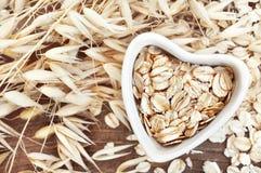 O groat da aveia no coração deu forma à bacia, grão da farinha de aveia para a dieta saudável no fundo das plantas das orelhas da imagens de stock