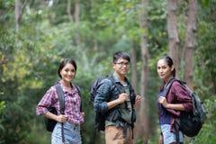 O grupo asiático de jovens que caminham com amigos backpacks walkin foto de stock
