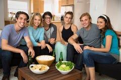O grupo atrativo do retrato de amigos reune para comemorar em casa para o partido do tempo do divertimento imagens de stock royalty free