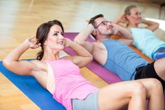 O grupo bonito do homem das mulheres está fazendo o esporte em um gym imagem de stock royalty free