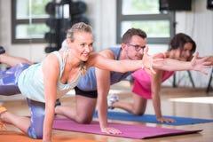 O grupo bonito do homem das mulheres está fazendo o exercício da aptidão do esporte em um gym foto de stock