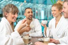 O grupo bonito novo est? fazendo o bem-estar com caf? e um champanhe fotografia de stock royalty free