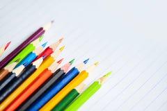 O grupo colorido do lápis no caderno do Livro Branco de volta à escola e ao conceito da educação/desenha colorido imagem de stock