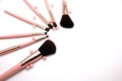 O grupo cosmético de compõe a escova em flatlay cor-de-rosa da cor e da pérola isolada em um fundo branco imagem de stock royalty free
