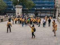 O grupo da excursão em revestimentos do ouro recolhe British Museum exterior, Londo Fotografia de Stock Royalty Free