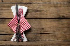 O grupo da forquilha e da faca com branco vermelho verificou o guardanapo em w rústico velho foto de stock