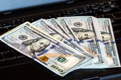 O grupo das notas de dólar jogadas em um teclado do portátil caracterizou bokeh defocused imagem de stock