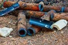 O grupo das tubulações oxidadas está encontrando-se na terra foto de stock