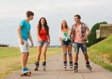 O grupo de adolescentes de sorriso com patina Imagem de Stock Royalty Free