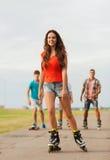 O grupo de adolescentes de sorriso com patina Fotos de Stock Royalty Free
