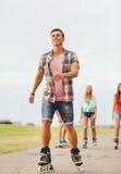 O grupo de adolescentes de sorriso com patina Foto de Stock Royalty Free