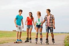 O grupo de adolescentes de sorriso com patina Fotografia de Stock