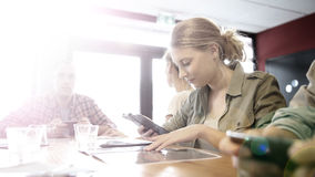 O grupo de adolescentes em um snack bar conectou no wifi público foto de stock royalty free