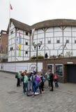 O grupo de adolescentes está na frente do theatr do globo do ` s de shakespeare foto de stock