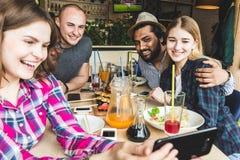 O grupo de amigos alegres novos est? sentando-se em um caf?, comendo, bebendo bebidas Os amigos tomam selfies e tomam imagens fotos de stock royalty free