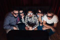 O grupo de amigos aprecia o filme do relógio nos vidros 3d imagens de stock
