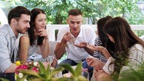 O grupo de amigos está conversando junto, comer e coctails da bebida no café video estoque