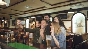 O grupo de amigos está tomando o selfie através do smartphone no bar agradável Os povos bonitos na roupa ocasional estão levantan vídeos de arquivo