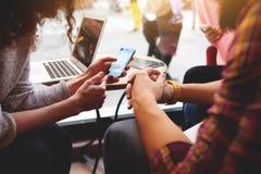 O grupo de amigos está usando dispositivos durante o tempo da recreação na cafetaria
