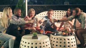 O grupo de amigos felizes que apreciam uma noite bebe video estoque