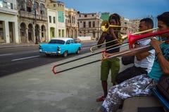 O grupo de amigos joga a música em Malecon em Havana, Cuba Imagens de Stock