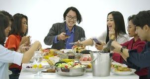 O grupo de amigos no partido de jantar com todos os povos na tabela usa seu smartphone tomando fotos do alimento do jantar vídeos de arquivo