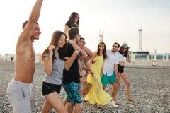 O grupo de amigos que andam na praia, tendo o divertimento, o reboque da mulher equipa sobre, férias engraçadas fotos de stock