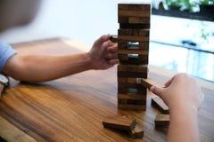 O grupo de amigos que jogam o jogo de madeira dos blocos na tabela dobrou o plutônio Imagens de Stock Royalty Free