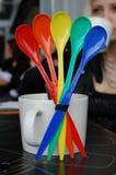 O grupo de arco-íris coloriu colheres na tabela no café Imagem de Stock