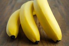 O grupo de bananas amarelas encontra-se em um fundo de madeira Imagem de Stock Royalty Free