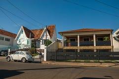 O grupo de casas na rua quieta com um carro do besouro estacionou na parte dianteira, em um dia ensolarado em São Manuel fotografia de stock royalty free