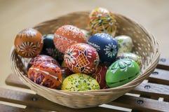 O grupo de cera pintou ovos da páscoa na luz - cesta de vime marrom Imagem de Stock Royalty Free