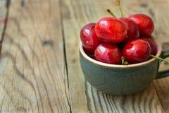 O grupo de cerejas doces lustrosas coloridas maduras frescas no copo de chá cerâmico no fundo de madeira, minimalista, copia o es Imagem de Stock