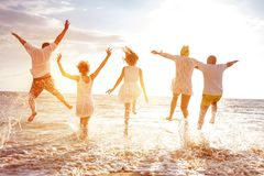 O grupo de cinco povos corre e salta ao mar do por do sol Fotos de Stock