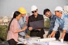 O grupo de coordenadores e os arquitetos discutem em um canteiro de obras fotos de stock