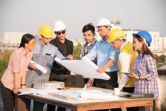 O grupo de coordenadores e os arquitetos discutem em um canteiro de obras imagens de stock