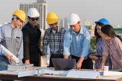 O grupo de coordenadores e os arquitetos discutem em um canteiro de obras imagem de stock