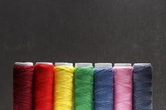 O grupo de cores pastel rosqueia costurando em um fundo preto Grupo de linhas no estilo retro das bobinas Acessórios do vintage p fotografia de stock