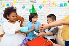 O grupo de crianças dá presentes ao menino do aniversário no chapéu festivo O menino é deleitado com presentes Fotos de Stock Royalty Free