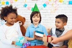 O grupo de crianças dá presentes ao menino do aniversário no chapéu festivo O menino é deleitado com presentes Imagens de Stock Royalty Free