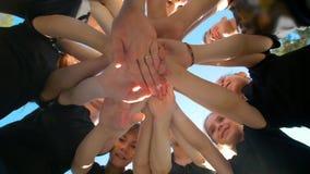 O grupo de crianças da escola executa o cumprimento inspirador dos esportes com as mãos no campo de jogos do futebol da jarda no  video estoque