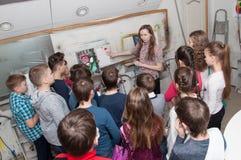 O grupo de crianças da pintura dos adolescentes com um aerógrafo coloriu brilhantemente imagens em um estúdio artístico - Rússia, Imagem de Stock