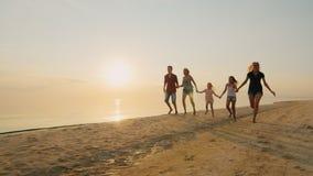 O grupo de crianças despreocupadas de idades diferentes e os adultos têm o divertimento que corre na praia filme