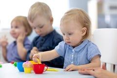O grupo de crianças dos bebês contratadas dentro handcrafts fotos de stock