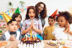 O grupo de crianças exulta do bolo com velas ardentes ocasionalmente do aniversário Fotos de Stock Royalty Free