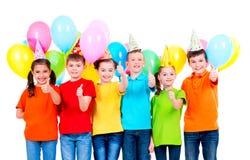 O grupo de crianças felizes nos chapéus do partido que mostram os polegares levanta o sinal imagens de stock royalty free